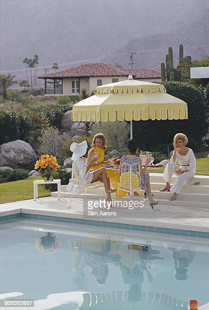 Ladies by the pool at the Kaufmann Desert House in Palm Springs California January 1970 From right to left former fashion model Helen Dzo Dzo Kaptur...