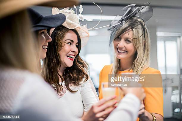 ladies celebrating the melbourne cup in the offfice - horse racing stock pictures, royalty-free photos & images
