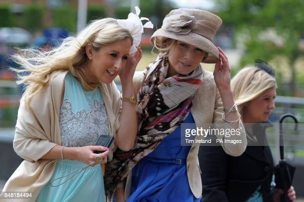 Ladies clutch their hats against the wind as they arrive during day four of the 2012 Royal Ascot meeting at Ascot Racecourse, Berkshire.