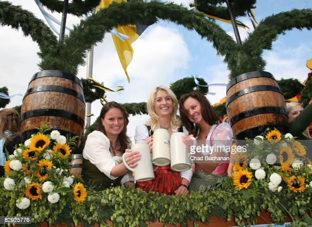 Ladies dressed in traditional Bavarian dirndls 'prosit' in beer carts at the Oktoberfest opening parade on September 20 2008 in Munich Germany The...