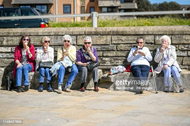 Ladies eat icecream on the promenade in WestonsuperMare where people are enjoying the warm weather