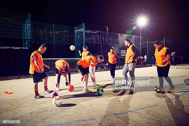 a ladies football team training under floodlights - kick line stock photos and pictures