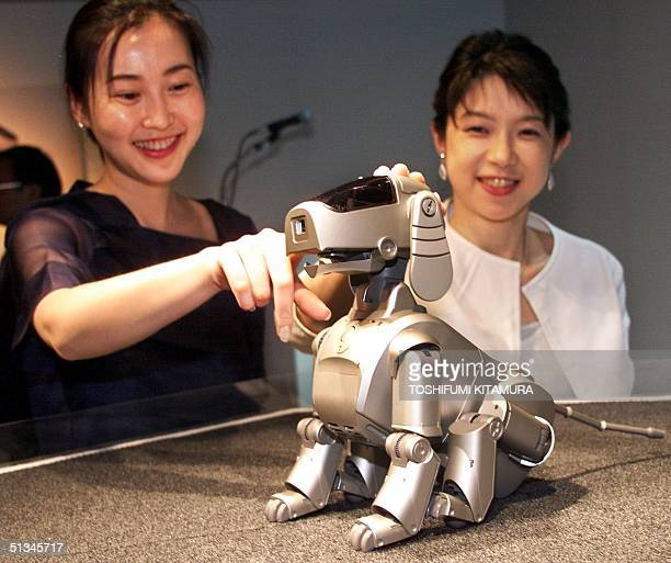 Ladies from Sony Corporation's PR section play with the company's new entertainment robot 'Aibo' during its press preview 11 May 1999 in Tokyo Sony...
