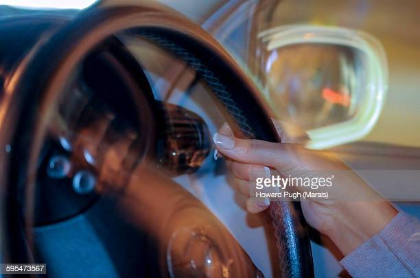 Ladies hand on motion blurred steering wheel