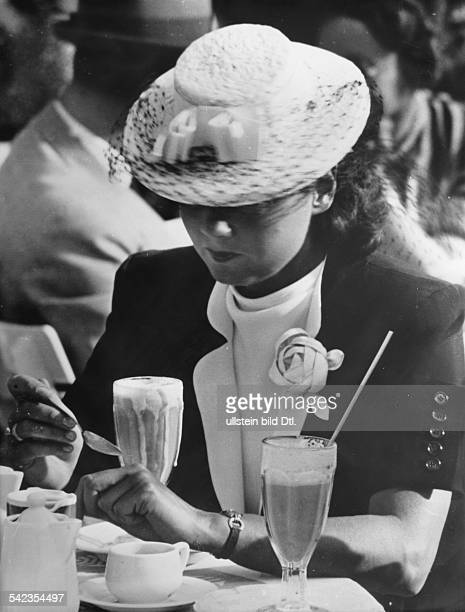 Ladies hats in the 1930ies Woman with an elegant hat having an iced chocolate drink undated probably 1939 Photographer Hanns Hubmann Vintage property...