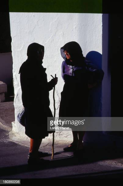 Ladies in black, talking in the shadows, hooded and in traditional dress - Krista, Lassithi Province, Crete