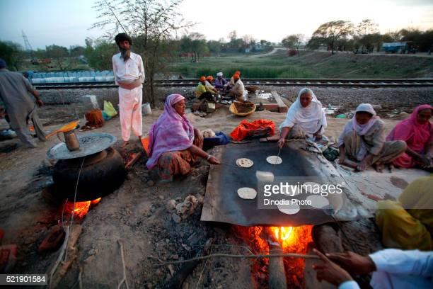 ladies making rotis cooked in large vessel in community kitchen at anandpur sahib in rupnagar district, punjab, india - punjab india stock pictures, royalty-free photos & images