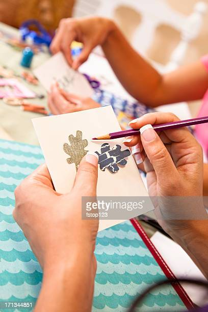 Ladies scrapbooking, considering ribbons and  trims on photograph.