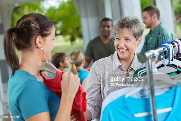 ladies shopping together for donated second hand clothing - garage sale stock pictures, royalty-free photos & images