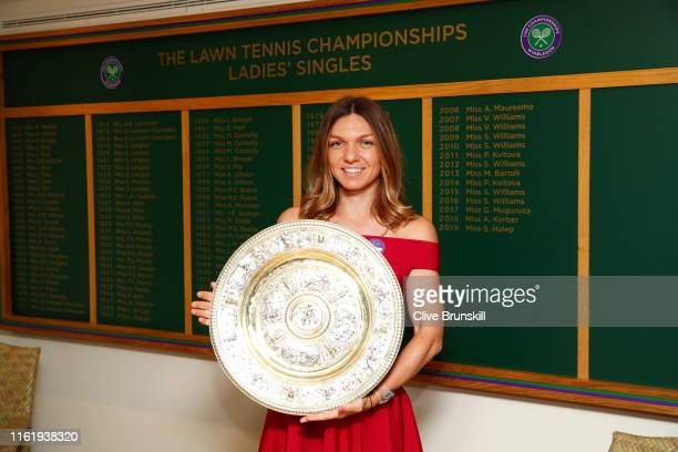 Ladies' Singles Champion Simona Halep of Romania poses for a photo with the trophy next to the winners board during Day thirteen of The Championships...