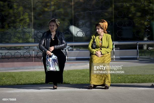 Ladies sit at a bus stop as a motorcade ferrying US Secretary of State John Kerry drives past on November 3 2015 in Ashgabat Kerry is traveling to...