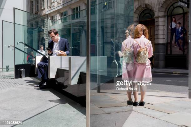 Ladies talk and a man uses his phone while sitting in sunshine during the lunchtime break on Threadneedle Street in the City of London the capital's...