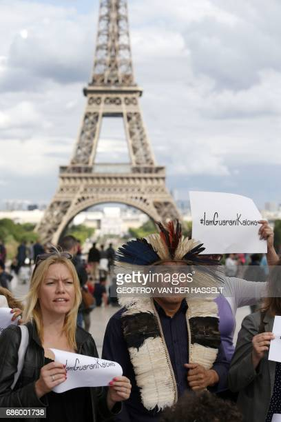 Ladio Veron a leader of Brazil's indigenous Guarani Kaiowa tribe stands with supporters in front of the Eiffel tower on May 20 2017on the Parvis des...