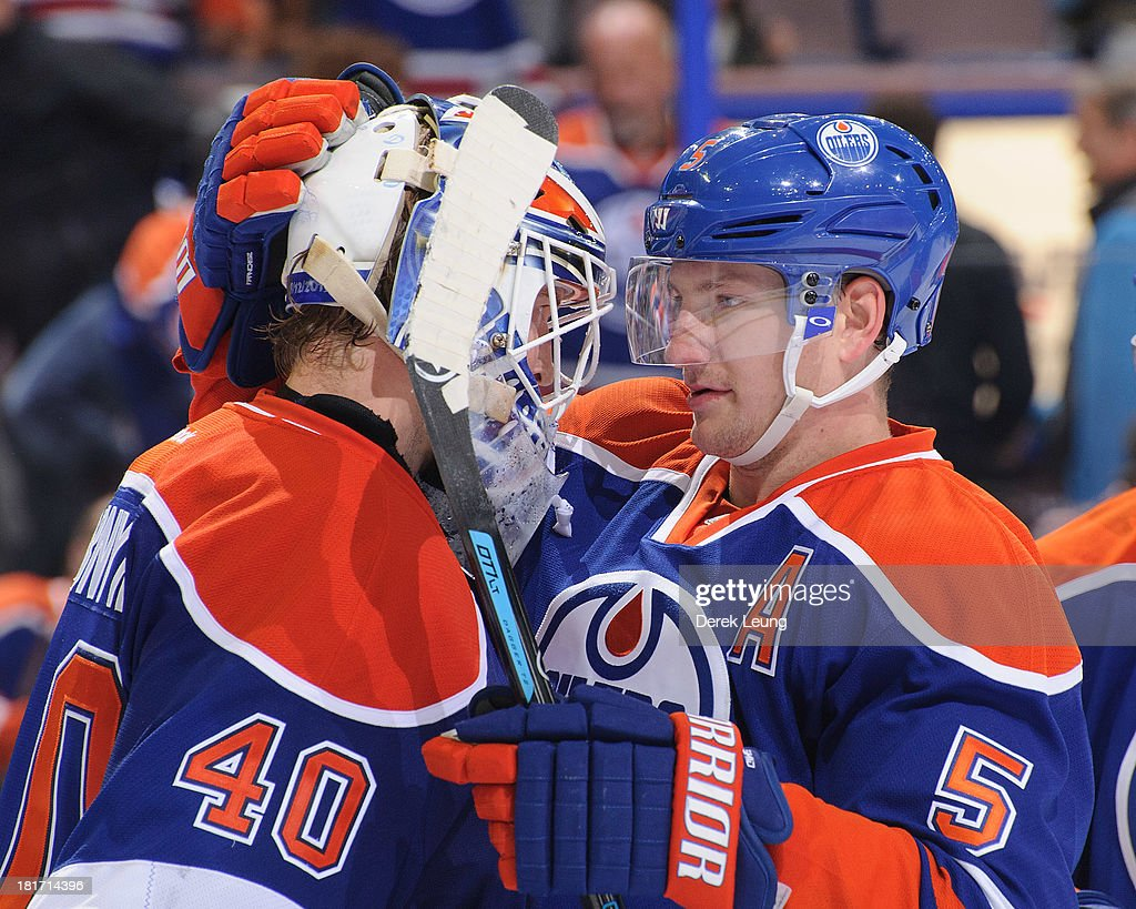Ladislav Smid #5 and Devan Dubnyk #40 of the Edmonton Oilers embrace each other after their win over the Winnipeg Jets during a preseason NHL game at Rexall Place on September 23, 2013 in Edmonton, Alberta, Canada.