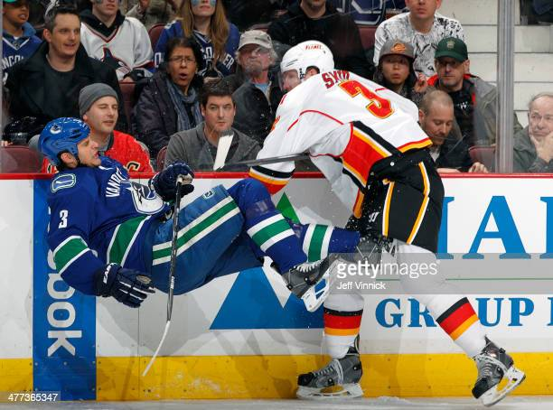 Ladislav Smid of the Calgary Flames checks Kevin Bieksa of the Vancouver Canucks during their NHL game at Rogers Arena March 8 2014 in Vancouver...