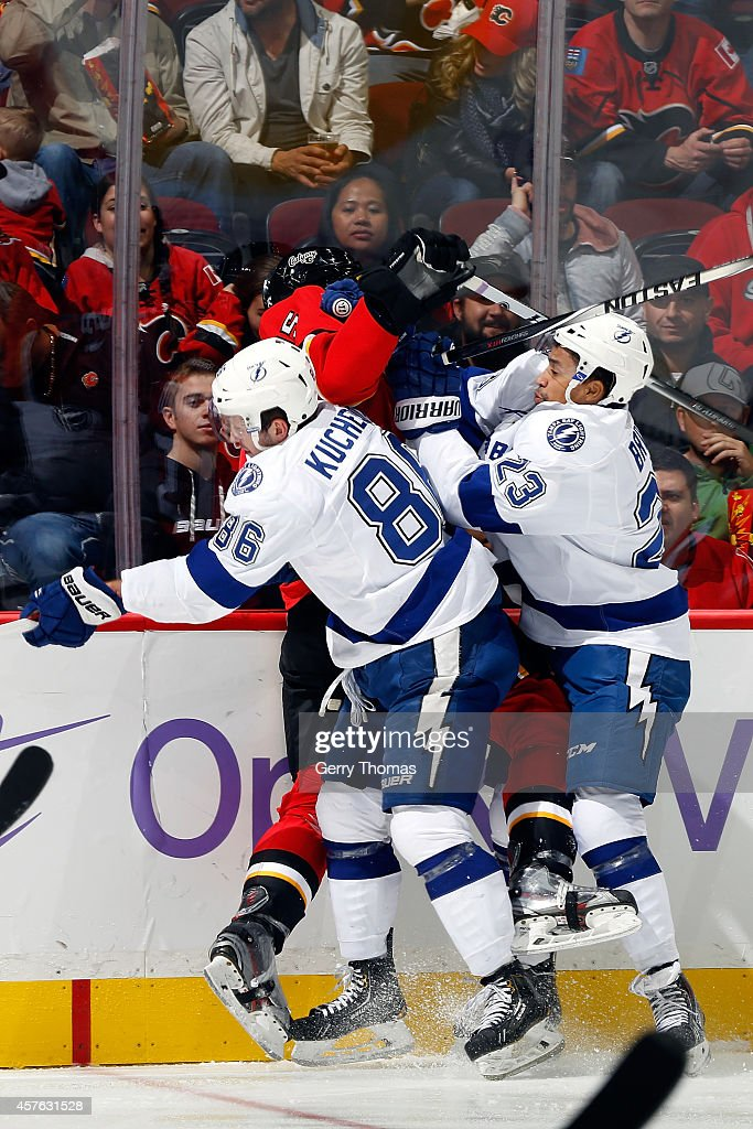Ladislav Smid #15 of the Calgary Flames is checked by Nikita Kucherov #86 and JT Brown #23 of the Tampa Bay Lightning at Scotiabank Saddledome on October 21, 2014 in Calgary, Alberta, Canada.
