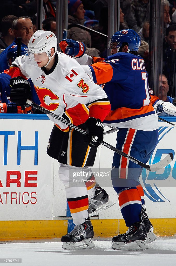 Ladislav Smid #3 of the Calgary Flames is shoved by Cal Clutterbuck #15 of the New York Islanders during an NHL hockey game at Nassau Veterans Memorial Coliseum on February 6, 2014 in Uniondale, New York. The Flames defeated the Islanders 4-2.