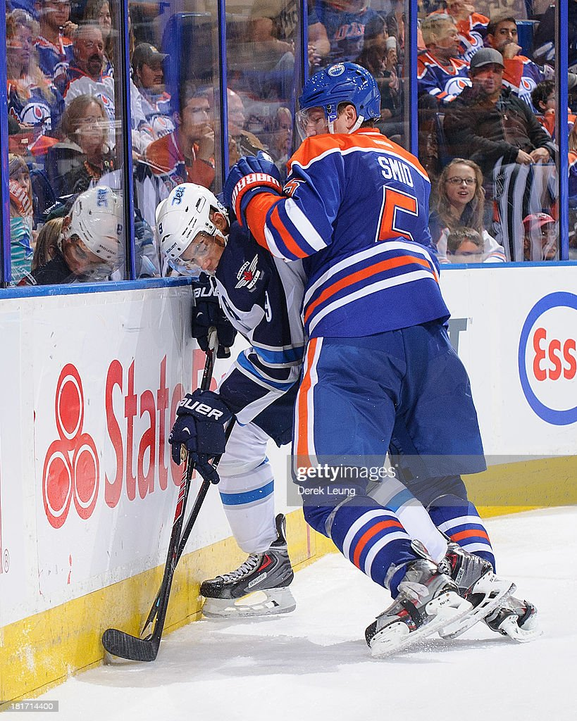 Ladislav Smid #5 of the Edmonton Oilers checks Evander Kane #9 of the Winnipeg Jets during a preseason NHL game at Rexall Place on September 23, 2013 in Edmonton, Alberta, Canada.