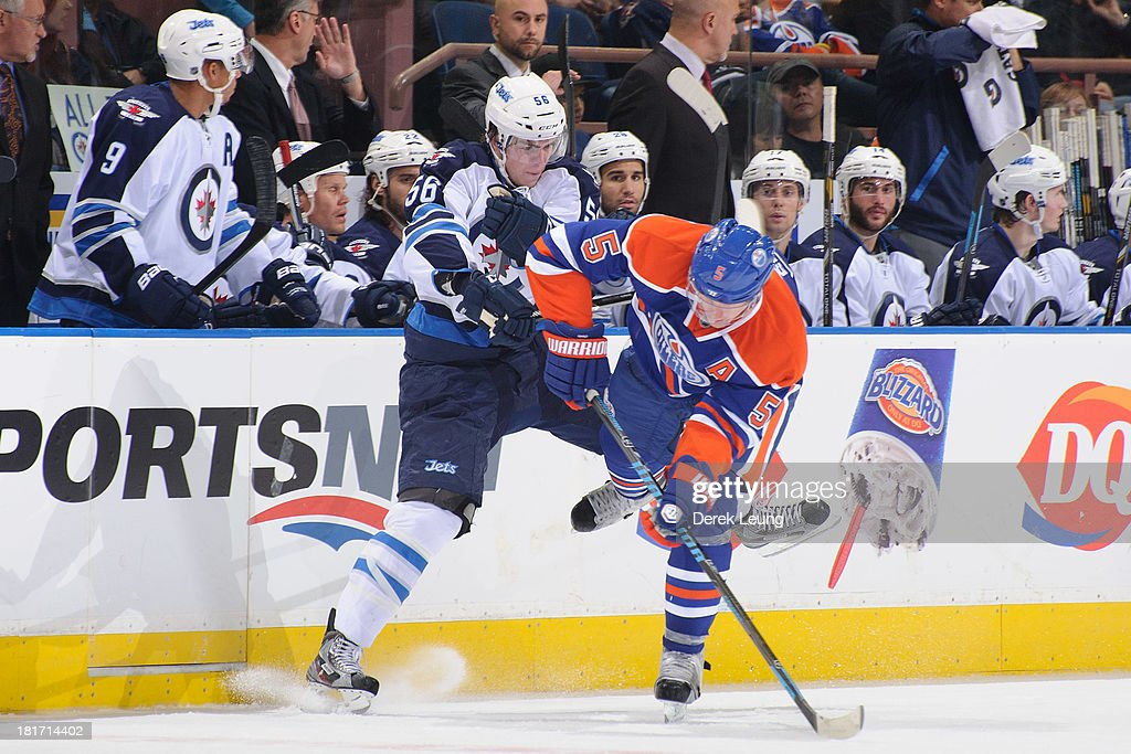 Ladislav Smid #5 of the Edmonton Oilers collides with Adam Lowry #56 of the Winnipeg Jets during a preseason NHL game at Rexall Place on September 23, 2013 in Edmonton, Alberta, Canada.
