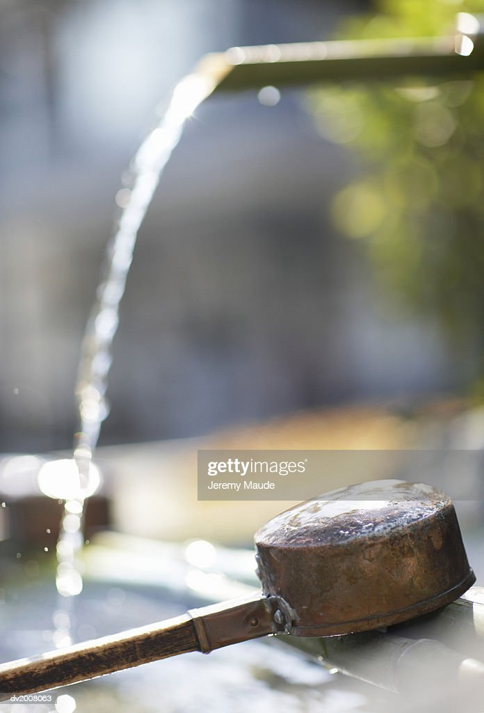 Ladle and Water Running From a Pipe, Japan : Stock Photo