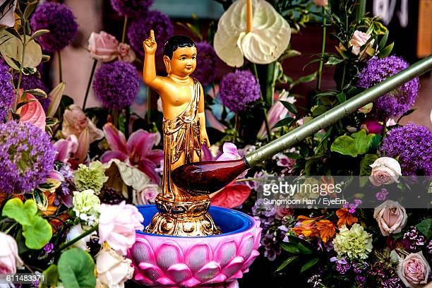 ladle pouring liquid on buddha figurine during festival - buddha's birthday stock pictures, royalty-free photos & images