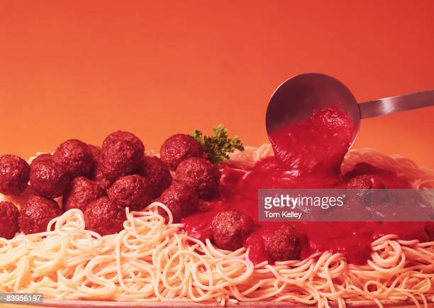 Ladle pours sauce onto a plateful of spaghetti and meatballs, ca.1950s. United States. Photo by Tom Kelley/Getty Images)