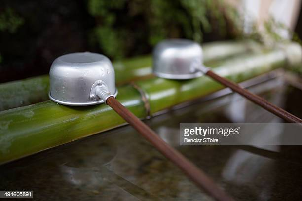 Ladles resting on bamboo over pure water in a Japanese Shinto shrine or Buddhist temple in Tokyo. Clear reflections on the water.