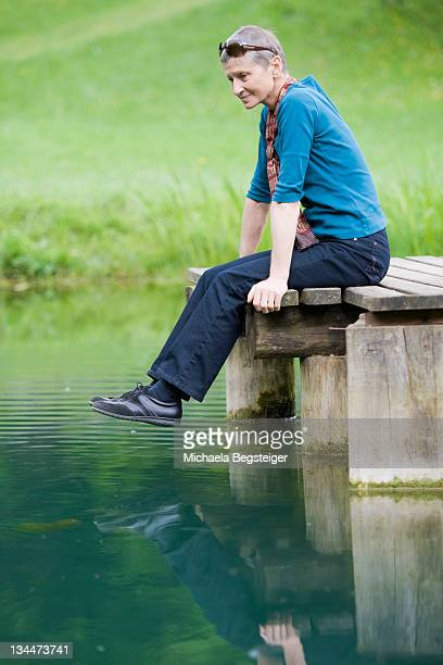Lady, 60 plus, sitting on a jetty at a pond