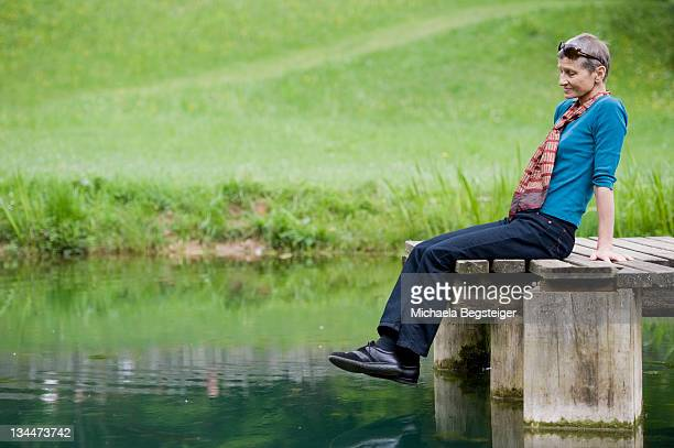 lady, 60 plus, sitting on a jetty at a pond - vista lateral stock pictures, royalty-free photos & images