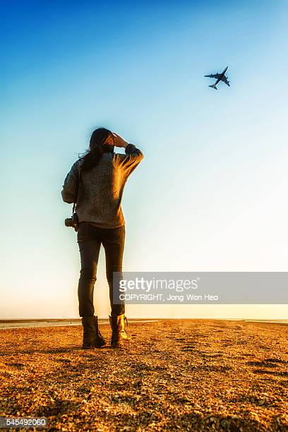 A lady and an airplane flying over her
