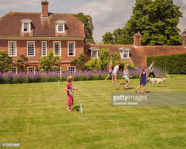 Lady Annabel Astorís grandsons and friends are photographed with Emily Sheffieldís dog Lilly playing croquet for Vanity Fair Magazine on June 22 2014...