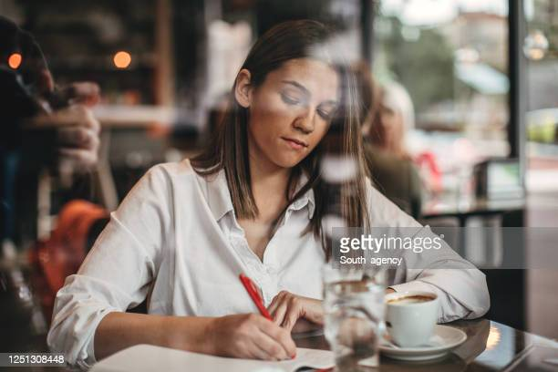 lady author sitting in cafe and writing notes in notebook - authors foto e immagini stock
