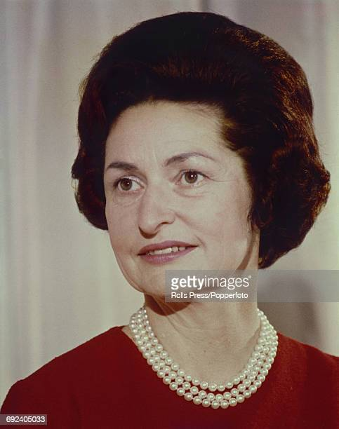 Lady Bird Johnson First Lady and wife of United States President Lyndon B Johnson posed wearing a red dress and pearl necklace in the United States...