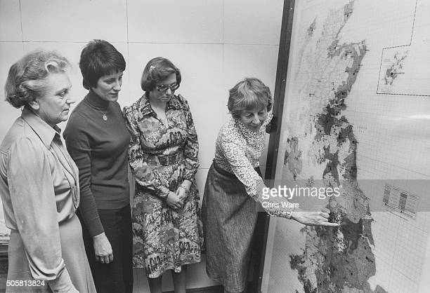 Lady Bridget Plowden Vice Chairman of the Independent Broadcasting Authority pointing out various TV stations on a large UK map to Shirley Muir...