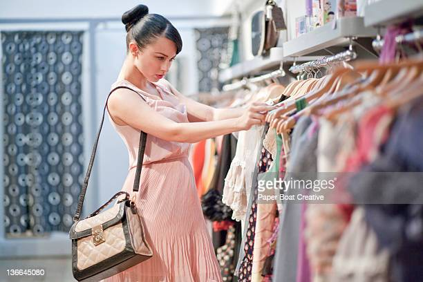 lady browsing through a clothes rail of dresses - abito senza maniche foto e immagini stock