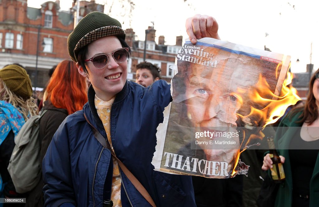 A lady burns the front page of a newspaper displaying an image of former British Prime Minister Margaret Thatcher as she and others celebrate her death in Brixton on April 8, 2013 in London, England. Lady Thatcher has died this morning following a stroke aged 87. Margaret Thatcher was the first female British Prime Minster and governed the UK from 1979 to 1990. She led the UK through some turbulent years and contentious issues including the Falklands War, the miners' strike and the Poll Tax riots.