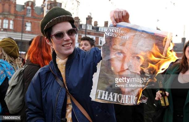 A lady burns the front page of a newspaper displaying an image of former British Prime Minister Margaret Thatcher as she and others celebrate her...