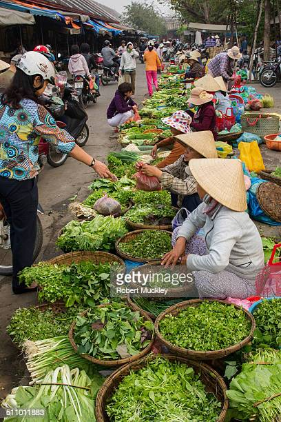 Lady buying greens at busy Hoi An market.
