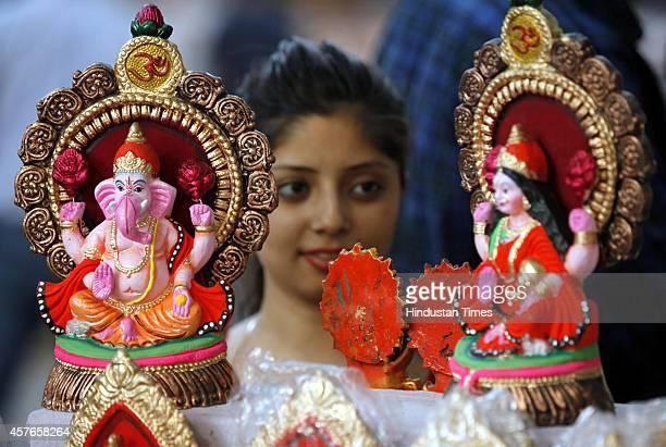 A lady buys idols of goddess Laxmi and lord Ganesha from roadside stalls eve of Hindu festival Diwali on October 22 2014 in New Delhi India Diwali...