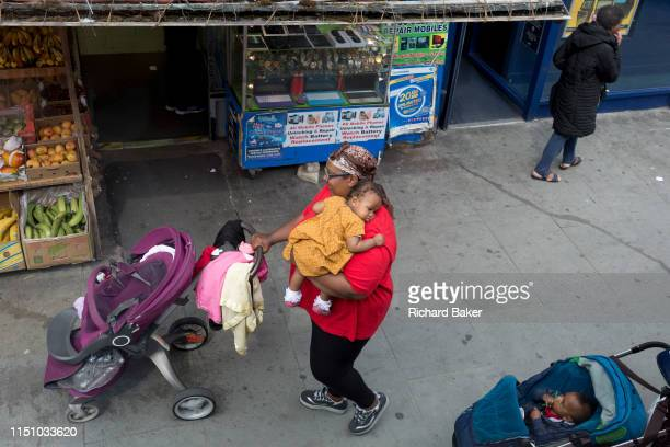 A lady carries a child past a fruit and vegetable shop in Camberwell Southwark on 18th June 2019 in London England