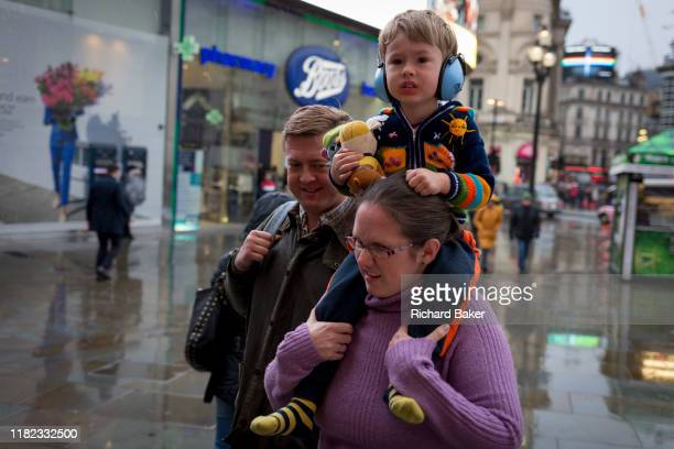 A lady carries a young child on her shoulders during a rain show at Piccadilly Circus in the West End on 12th November 2019 in London England