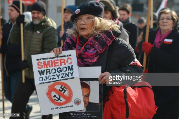 A lady carries 'Death to the enemies of the Motherland' sign during celebrations of the 'Cursed Soldiers' Day in Krakow The 'Cursed soldiers' applied...
