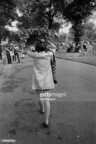Lady carrying a bouquet above her head on the last day of the Chelsea Flower Show, London, May 1968.