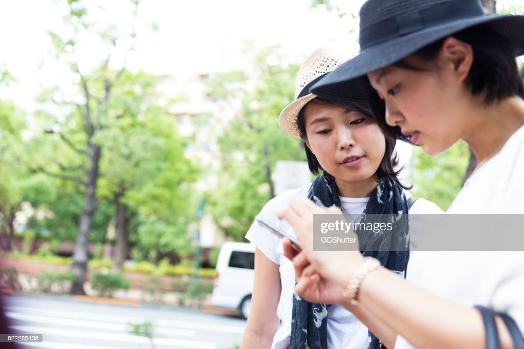 Lady checking her messages while walking : Stock Photo