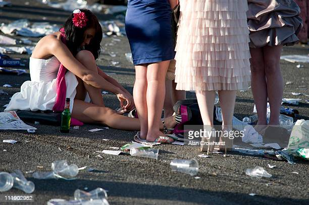 A lady checks her feet at the end of Ladies Day at Aintree racecourse on April 08 2011 in Liverpool England
