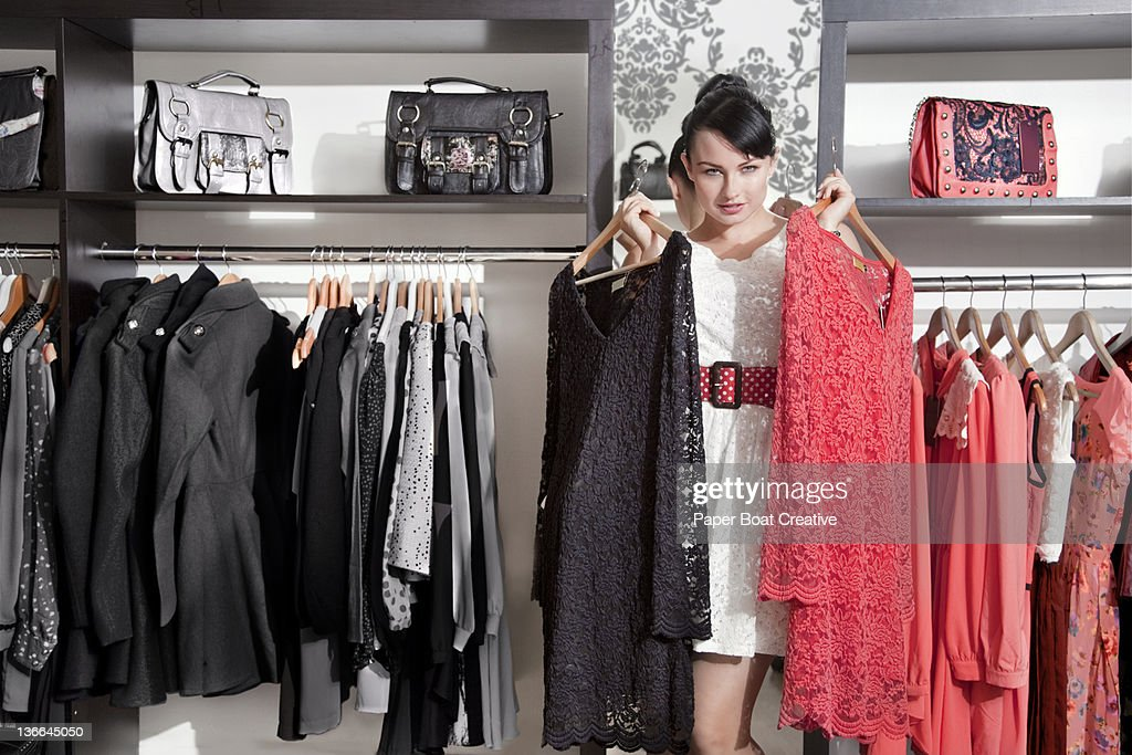 lady choosing between a red dress and black dress : Stock Photo
