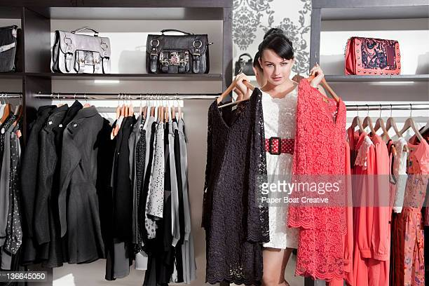 lady choosing between a red dress and black dress