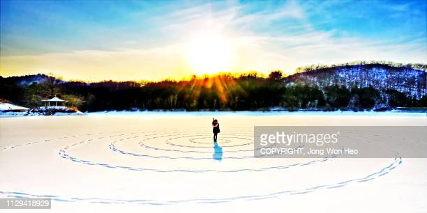 A lady communicating with the sun in the middle of the frozen lake