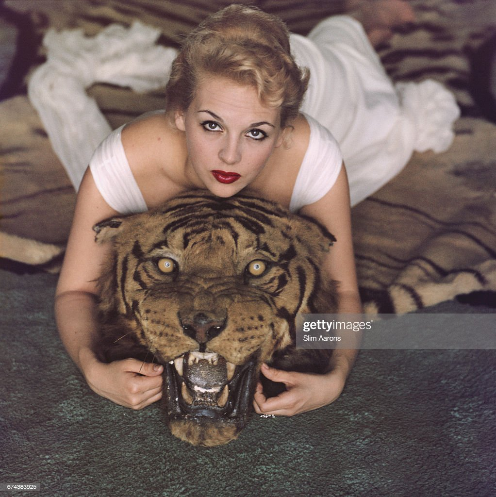 Lady Daphne Cameron (Mrs George Cameron) on a tiger skin rug in the trophy room at socialite Laddie Sanford's home in Palm Beach, Florida, 1959.