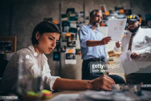 lady detective working late with colleagues - killing stock pictures, royalty-free photos & images